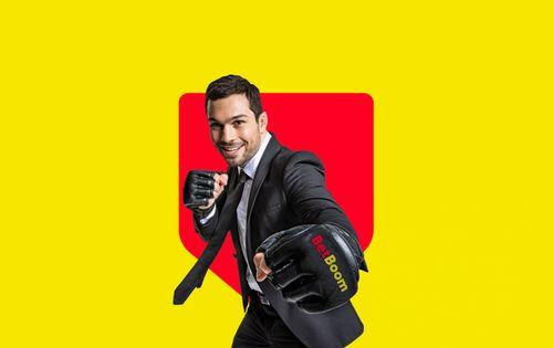 Мужчина в костюме и боксерских перчатках наносит удар, на перчатке написано новое название БК: BetBoom